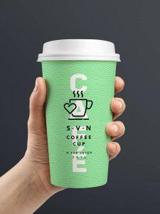 Ihminen pitelee kädessään vihreää kahvikuppia, joka on painettu