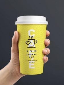 Ihminen pitelee kädessään keltaista kahvikuppoa, joka on painettu