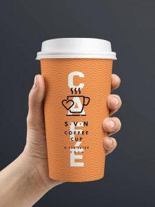 Ihminen pitelee kädessään oranssia kahvikuppia, joka on painettu